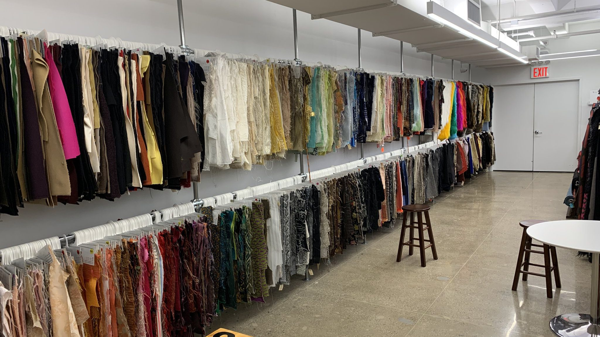 Hundreds of fabrics in a variety of textures and colors hanging on a white wall in two rows